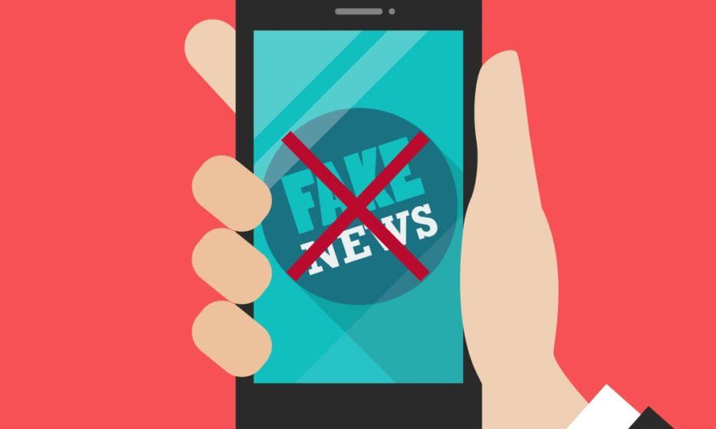 Ilustração de uma mão segurando um celular, onde se lê a expressão fake news e um grande X, simbolizando a necessidade de não disseminar/compartilhar fake news