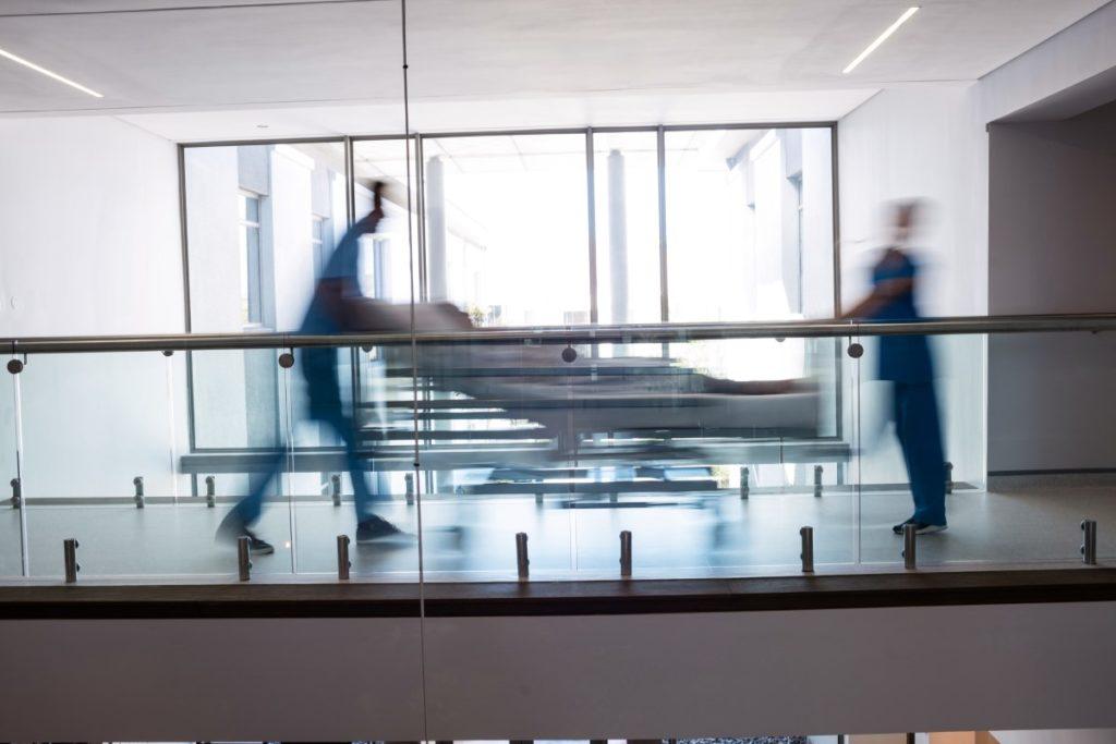 Imagem de médicos transportando paciente para unidade de tratamento intensivo em hospital.