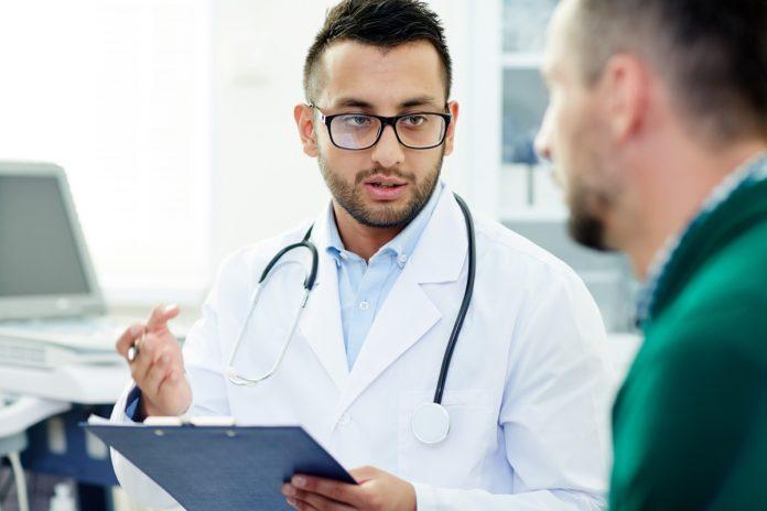 Imagem de médico conversando com paciente enquanto faz anotações, no texto sobre coberturas do plano de saúde no blog da Sami