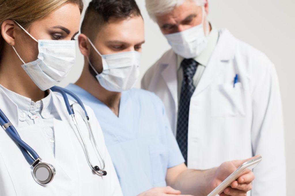 Imagem de time médico analisando informações de paciente através de aplicativo no celular.
