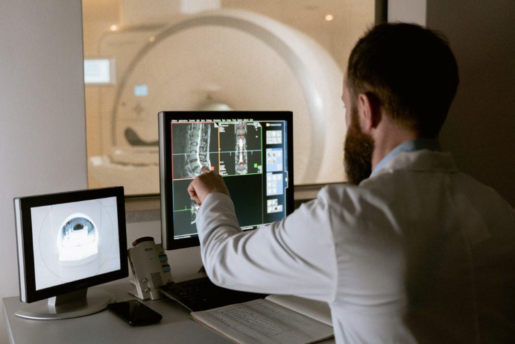 Imagem de médico especialista realizando exame de ressonância magnética em paciente.