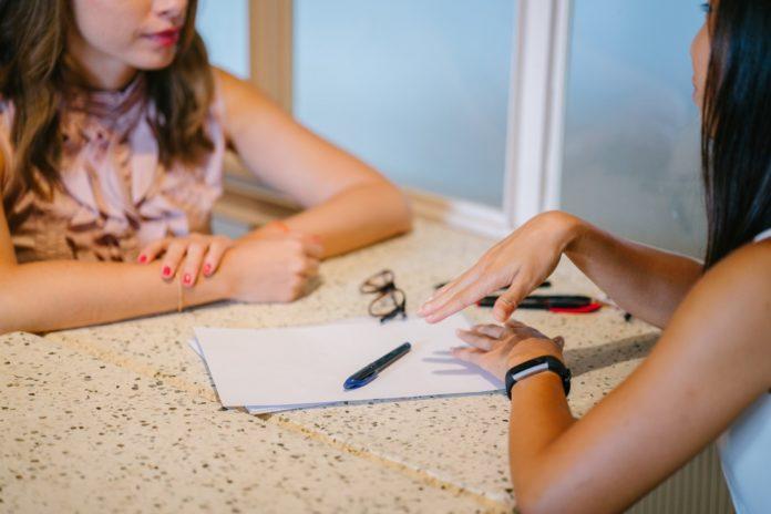 Imagem de duas mulheres conversando com documento sobre a mesa, imagem ilustrativa no texto sobre convenções coletivas e sua relação com plano de saúde no blog da Sami