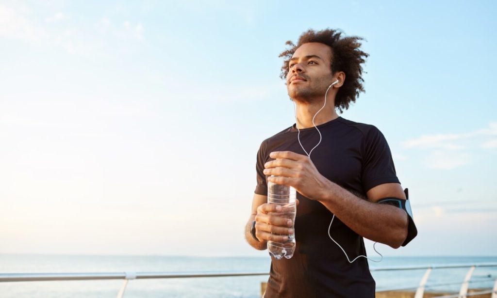 """Jovem preto, segurando garrafa de água, pratica corrida ao ar livre, escutando música. Para a OMS, o conceito de saúde é o """"completo bem-estar físico, mental e social"""", considerando por muitos uma utopia"""
