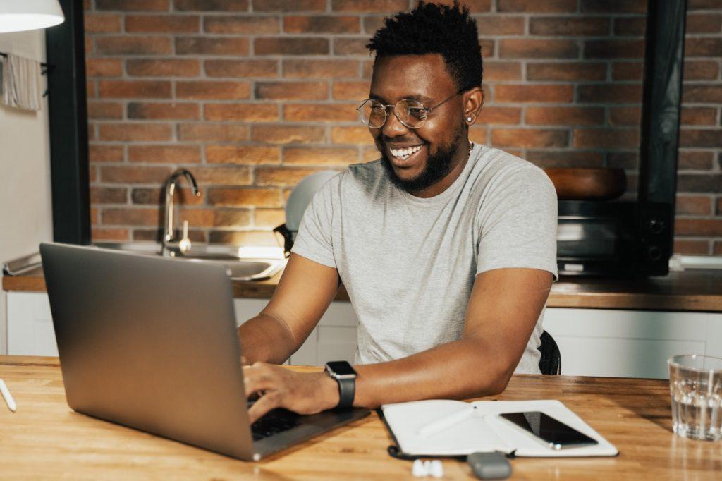 Imagem de homem negro profissional trabalhando em seu notebook, no texto sobre o tema: Quanto custa plano de saúde empresarial?