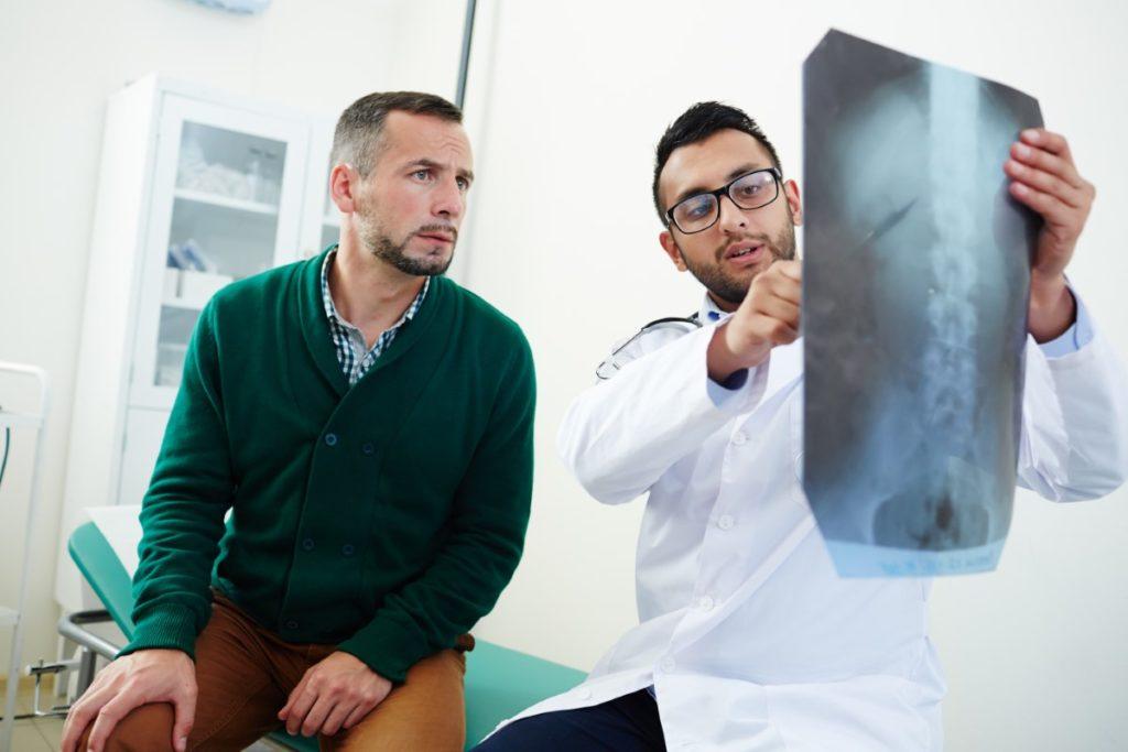 Imagem de médico explicando para paciente informações de um exame de imagem.