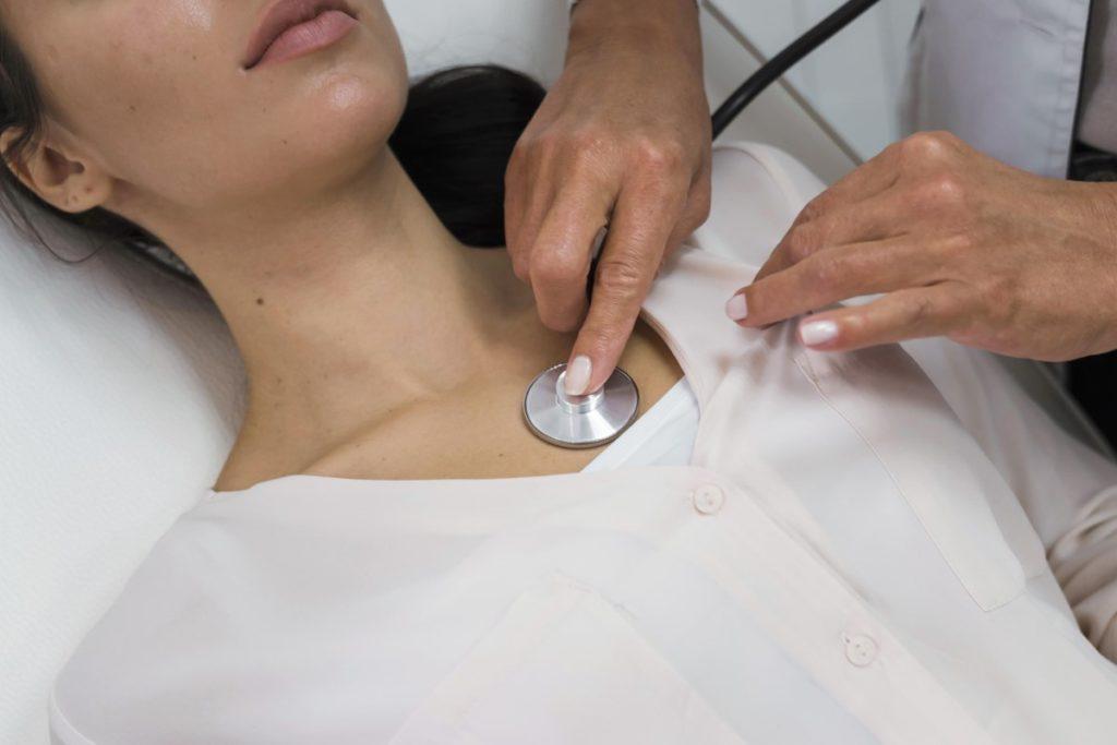 Imagem de médica medindo os batimentos cardíacos de sua paciente.