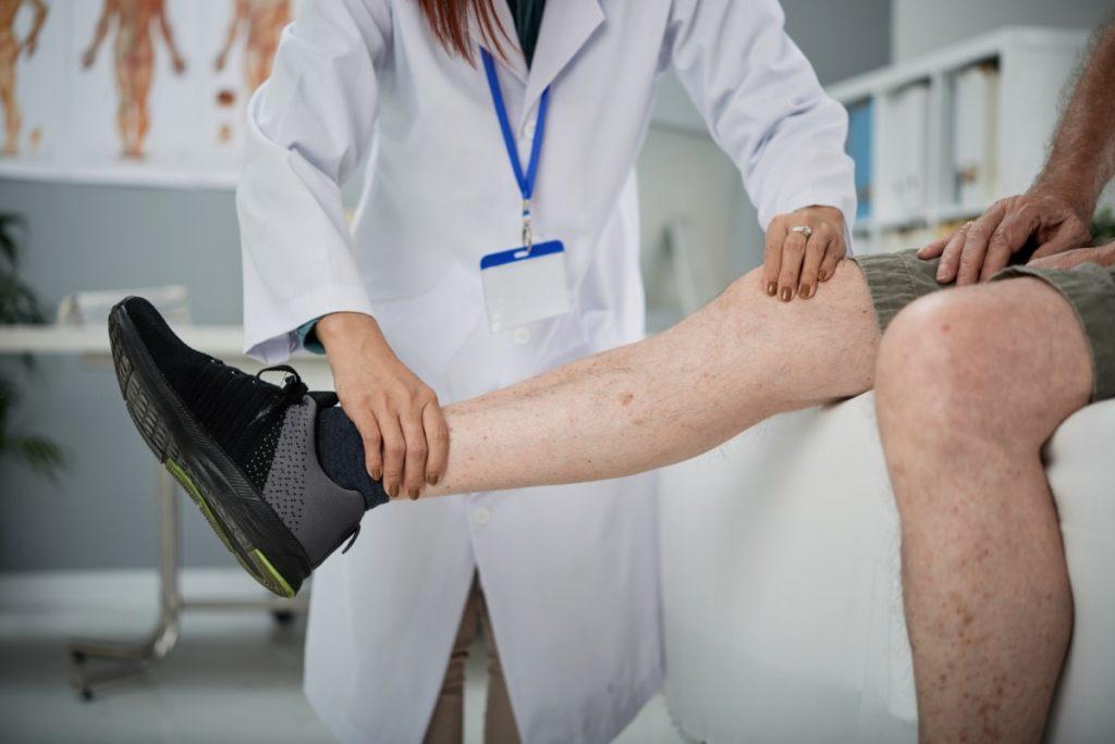 Imagem de médica examinando a perna de um paciente do sexo masculino.