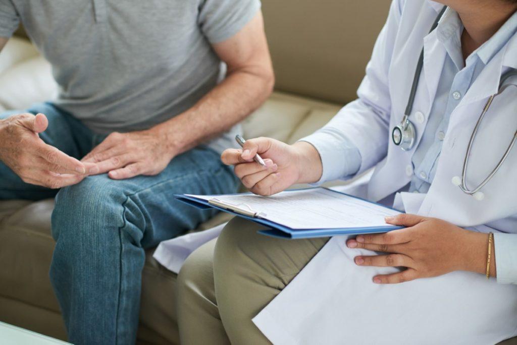 Imagem de médica preenchendo prontuário enquanto conversa com paciente.