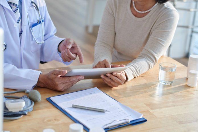 Imagem de paciente e médico discutindo informações do prontuário, presente no conteúdo sobre aproveitamento ou compra de carência no plano de saúde no blog da Sami.