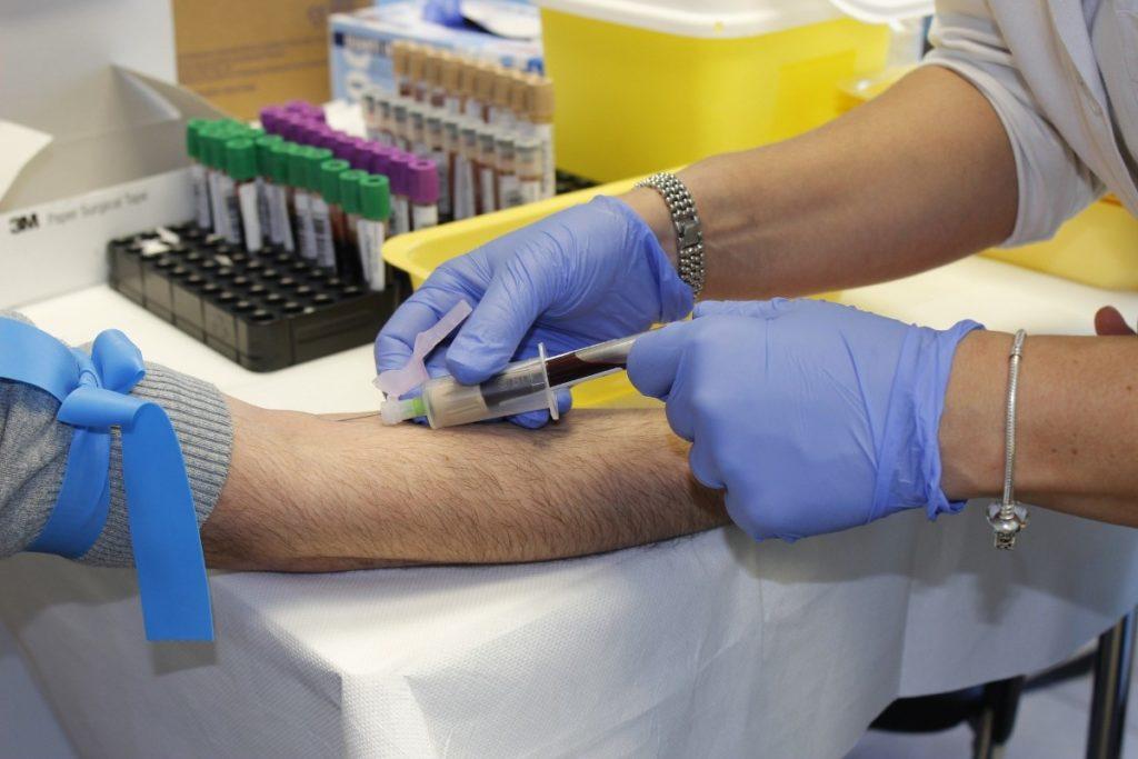 Imagem de médico colhendo sangue de paciente durante exame, presente no texto sobre cobertura parcial temporária (CPT) no blog da Sami.
