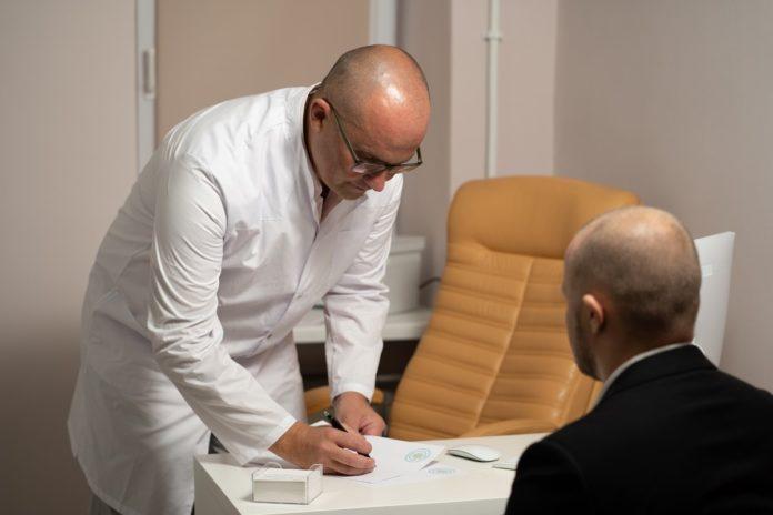 Imagem de médico escrevendo receita para paciente, no texto que esclarece o que são as doenças e lesões preexistentes no plano de saúde.