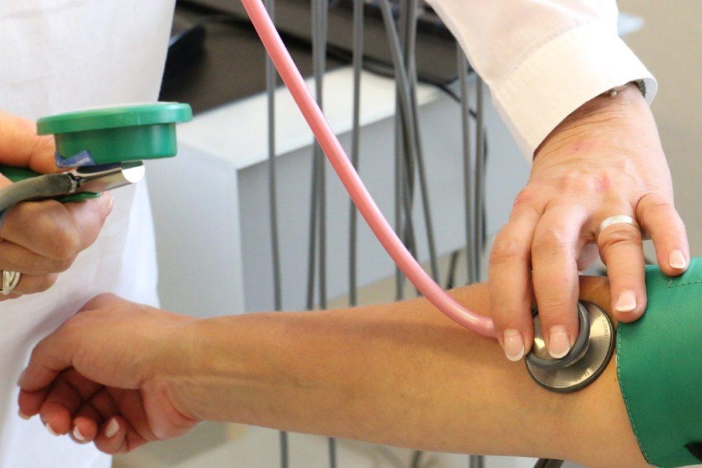 Imagem de médica fazendo um exame de frequência cardíaca em paciente.
