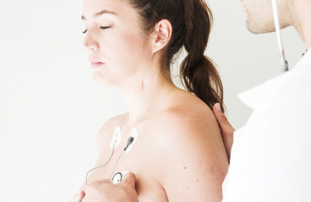 Imagem de paciente com sensores cardíacos sendo examinada por médico.