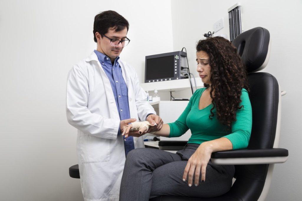 Imagem de médico enfaixando a mão de uma paciente.