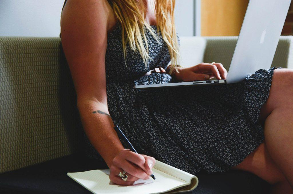 Imagem de empreendedora jovem, fazendo anotação enquanto utiliza notebook, presente no texto sobre pagamento do plano de saúde no blog da Sami