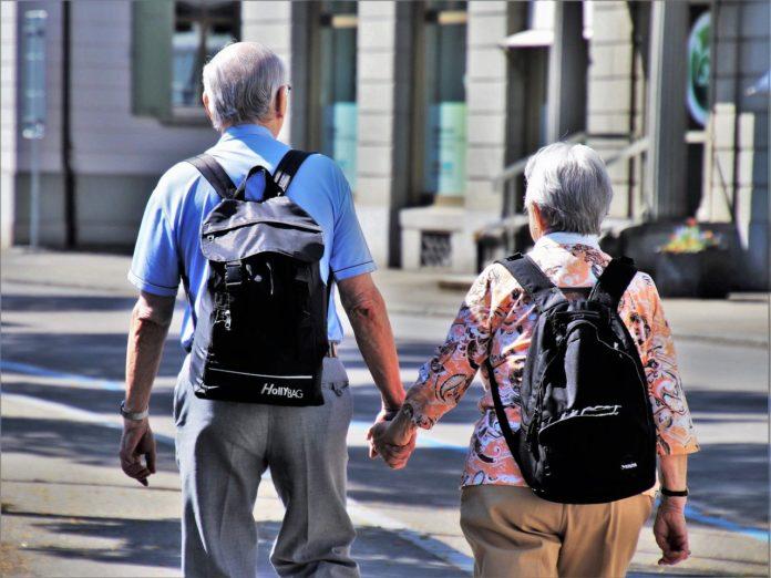 Imagem de dois idosos andando de mãos dadas com mochila nas costas, presente no texto sobre quanto custa o plano de saúde para idoso e por que é mais caro no blog da Sami
