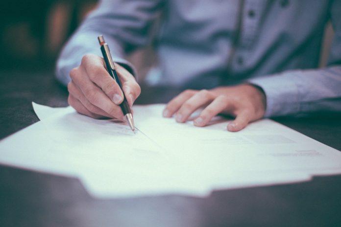 Imagem de homem assinando um contrato de plano de saúde, presente no texto sobre administradora de benefícios presente no blog da Sami