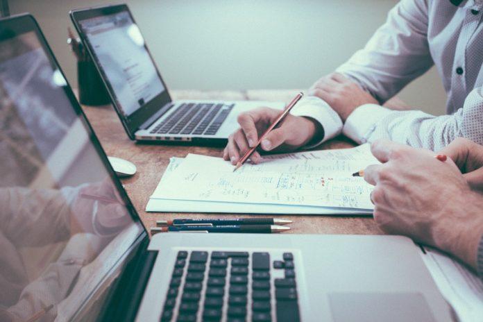 Imagem de dupla de empreeendedores analisando documentos com seus notebooks, presentes no texto sobre upgrade de plano de saúde empresarial no blog da Sami