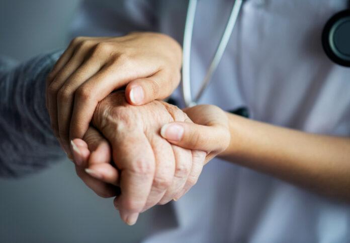 Imagem de enfermeira segurando a mão de paciente idoso, presente no texto do blog da Sami que explica o papel do(a) enfermeiro(a) na Atenção Primária à Saúde