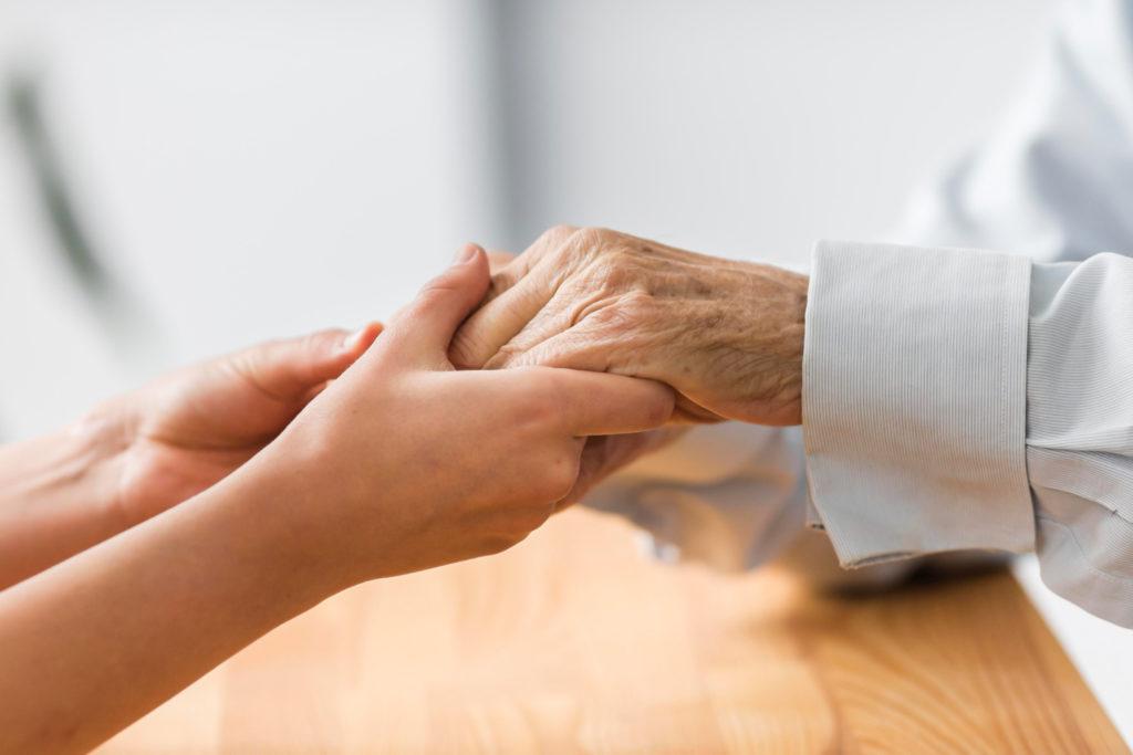 Imagem de enfermeira e idoso segurando as mãos, presente no texto sobre home care presente no blog da Sami