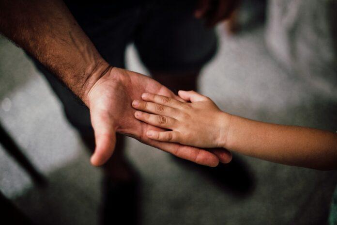 Imagem de pai e filho de mãos dadas, presente no texto do blog da Sami sobre o tema: plano de saúde cobre vasectomia?