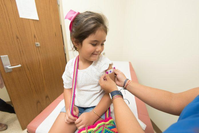Imagem de criança recebendo curativo no braço, presente no texto que fala sobre o papel do técnico de enfermagem na atenção primária no blog da Sami