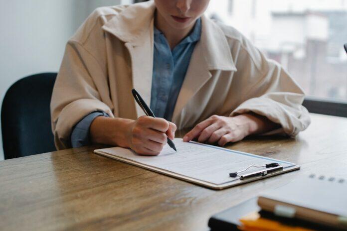 Imagem de jovem profissional anotando em folha de papel, presente no texto do blog da Sami que responde a pergunta: o que é franquia no plano de saúde?