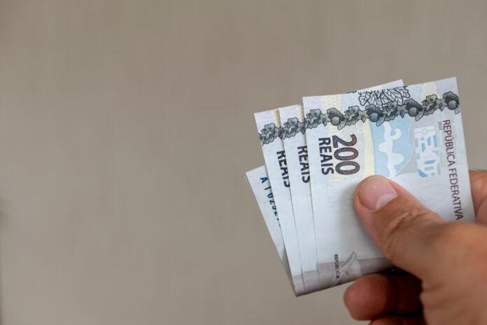 Imagem de notas de real na mão de pessoa realizando o pagamento do plano de saúde, no texto do blog da Sami que responde à dúvida: plano de saúde cancelado por falta de pagamento pode ser reativado?