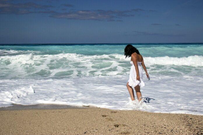 Imagem de jovem empreendedora curtindo férias na praia, presente no texto da Sami que responde à pergunta: