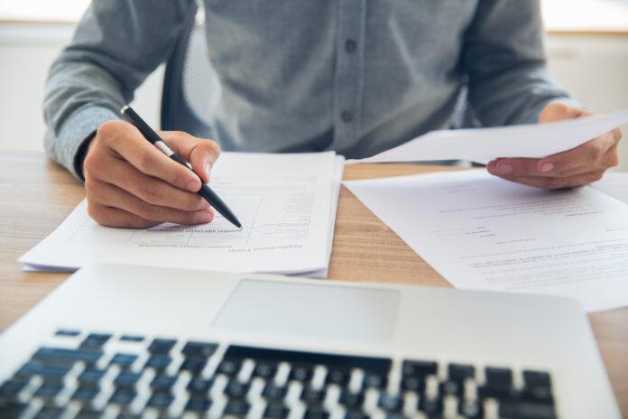 Imagem de jovem empreendedor lendo relatório de sinistralidade do plano de saúde do seu negócio, presente no texto sobre o tema no blog da Sami